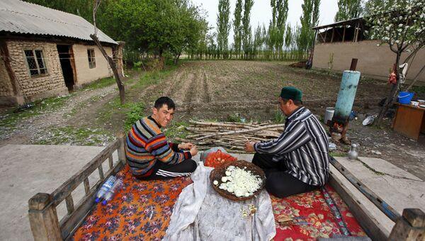 Жители села Тейит чистят лук во дворе своего дома