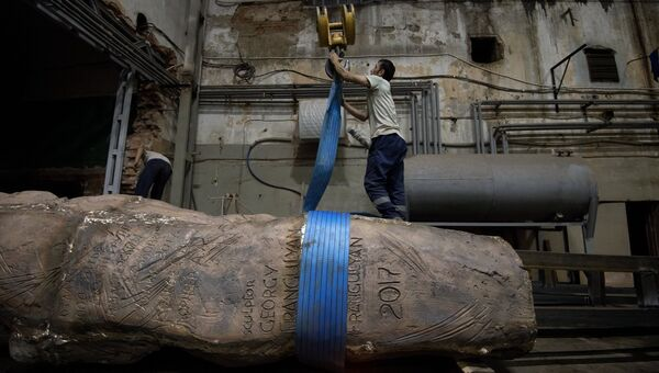 Рабочий закрепляет элементы конструкции монумента Стена скорби перед началом его транспортировки к месту установки в Москве