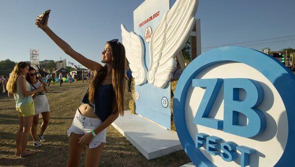 Девушка фотографируется на музыкальном фестивале #ZBFest в Балаклаве