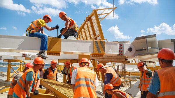 Рабочие на строительстве стадиона