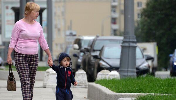 Женщина с ребенком идут по улице Житная в Москве