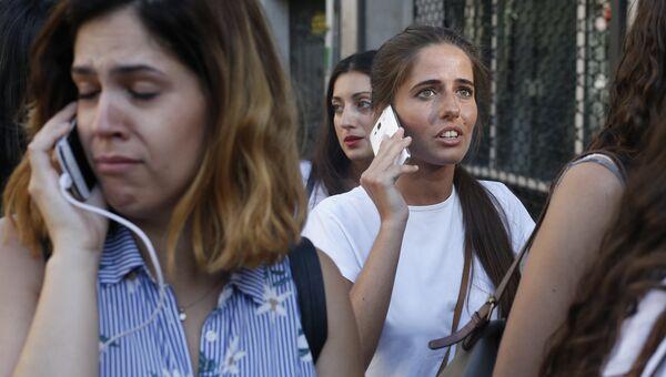 Люди звонят родственникам и друзьям после наезда микроавтобуса на пешеходов в Барселоне. 17 августа 2017