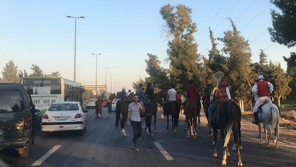 Сирийцы на автомобилях и лошадях едут в выставочный городок на южной окраине Дамаска, где открылась 59-я Международная промышленная выставка. 19 августа 2017