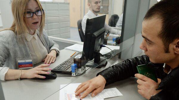 Иностранный гражданин разговаривает с сотрудником миграционного центра