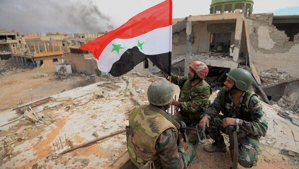 Военнослужащие САА с флагом Сирии радуются освобождению Пальмиры