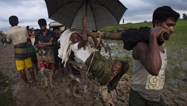 Этнические Рохинджа  Мьянма ислам мусульмане несут пожилого мужчину к Бангладешской границе. Архивное фото