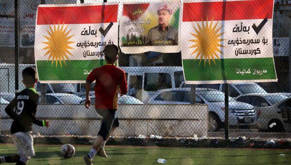 Дети играют в футбол на фоне плаката с изображением лидера иракских курдов Масуда Барзани. Архивное фото