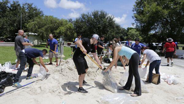 Волонтеры и местные жители подготавливают мешки с песком перед надвигающимся ураганом Ирма