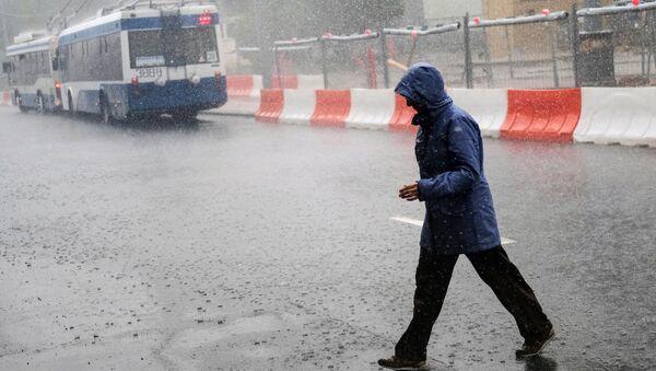 Прохожий во время ливня на одной из улиц Москвы. Архив