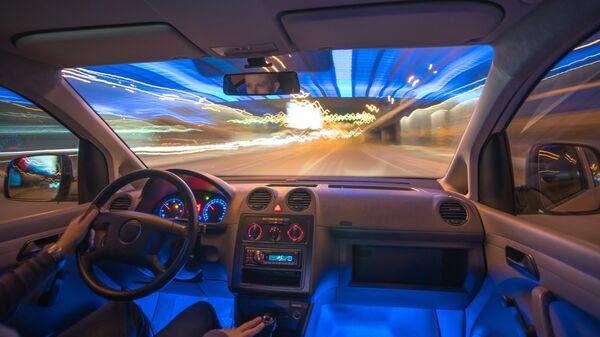 Мужчина за рулем автомобиля ночью. архивное фото