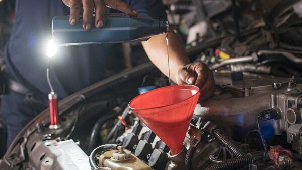 Мужчина заливает масло в двигатель автомобиля