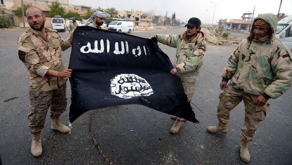 Бойцы сирийского отряда народного ополчения Соколы пустыни демонстрируют флаг Исламского государства (ИГ, запрещена в РФ)