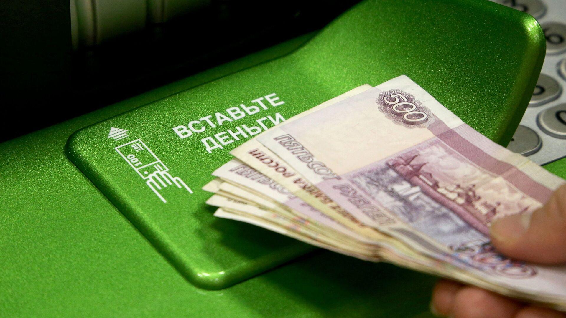 Посетитель банка вносит деньги в банкомат - РИА Новости, 1920, 23.10.2017