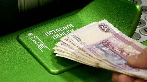 Посетитель банка вносит деньги в банкомат