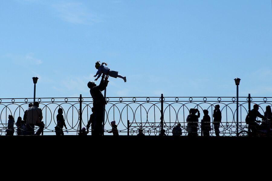 Мужчина с ребенком на набережной