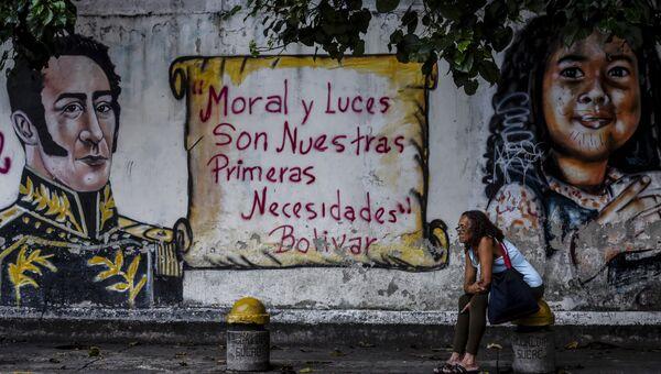 Женщина сидит около стены с граффити с цитатой Симона Боливара Мораль и просвещение - наша насущная необходимость напротив избирательного участка в Каракасе