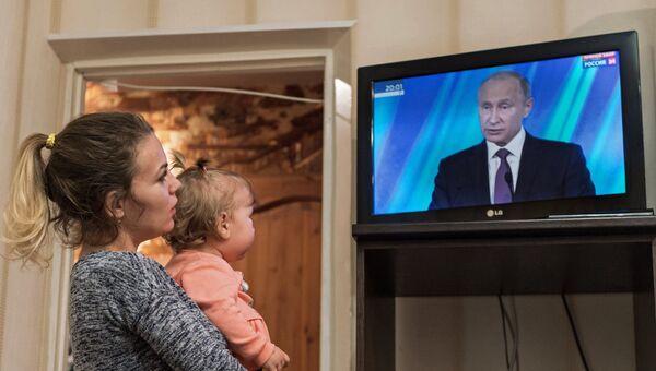 Жительница Омска смотрит трансляцию выступления президента РФ Владимира Путина на итоговой сессии международного дискуссионного клуба Валдай. 19 октября 2017