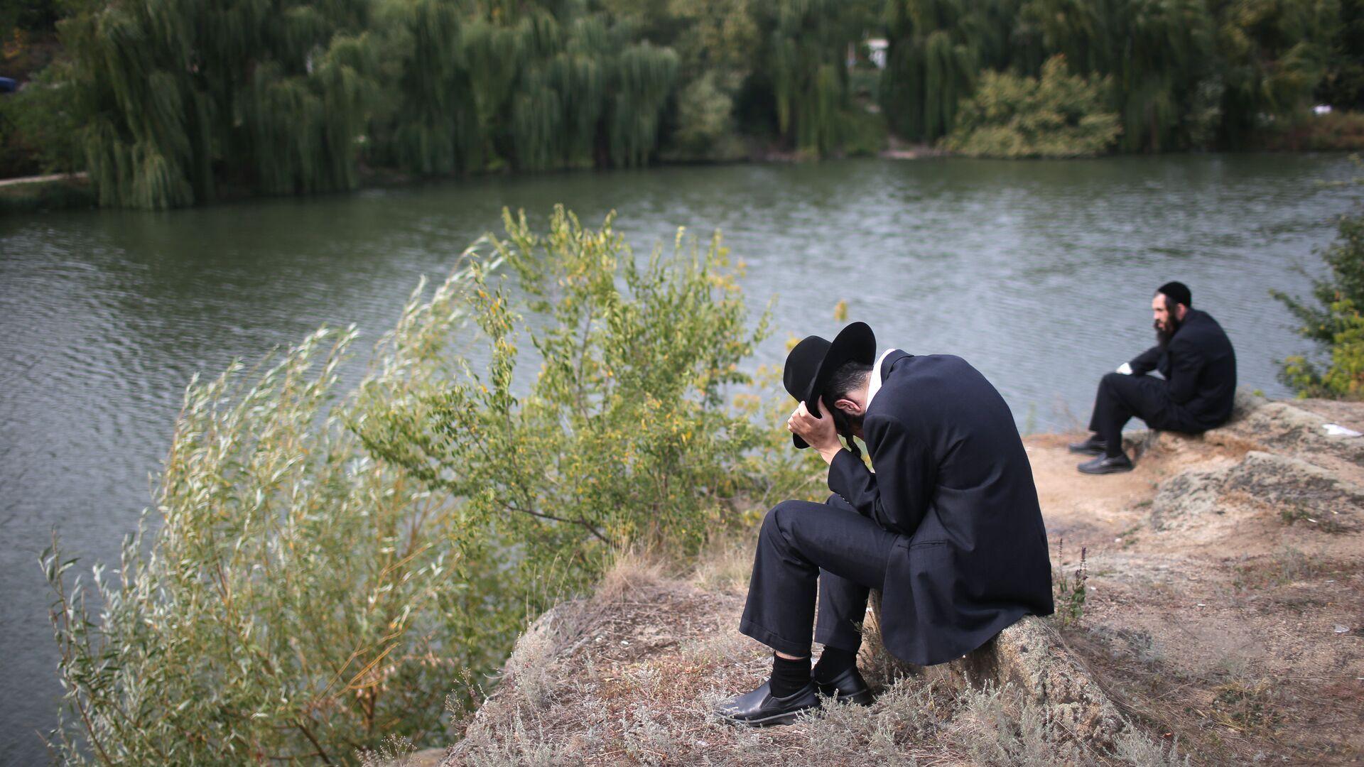 Паломник сидит на берегу реки в канун еврейского нового года на Украине - РИА Новости, 1920, 03.09.2020