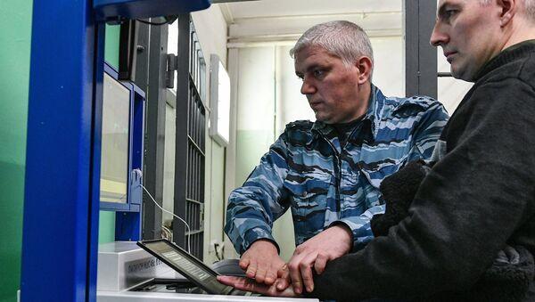 Сотрудник ФСИН России сканирует ладонь заключенного на многофункциональной дактилоскопической станции ПАПИЛОН МДС 45c в Следственном изоляторе № 2. 31 октября 2017
