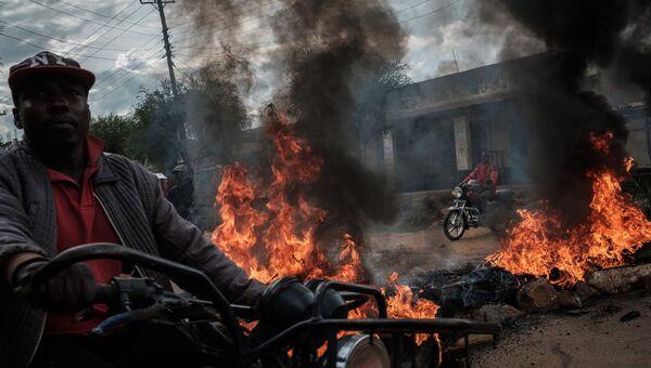 Водители мототакси проезжают мимо горящих баррикад во время протеста в Маенго, Кения