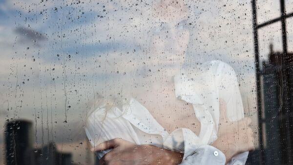 Девушка у окна во время дождя. Архивное фото