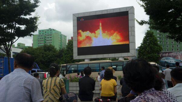 Жители КНДР смотрят репортаж о запуске межконтинентальной баллистической ракеты. Архивное фото