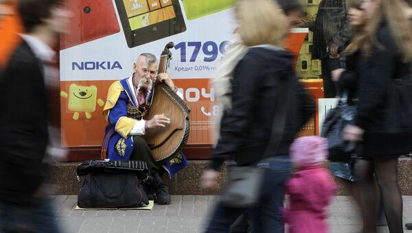 Уличный музыкант исполняет с домрой на улице Киева. 18 апреля 2013