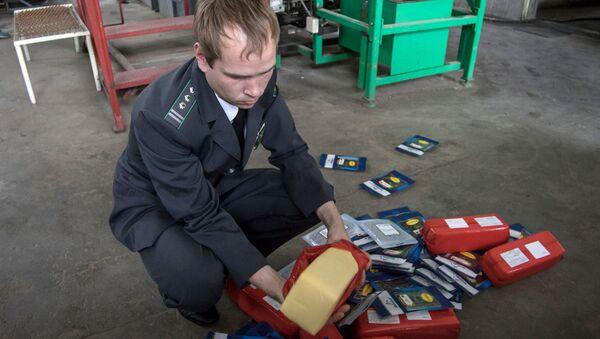 Сотрудник таможенной государственной службы демонстрирует санкционные продукты, подлежащие уничтожению