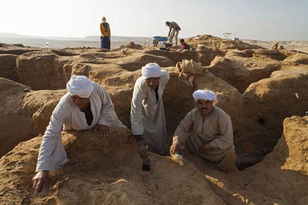 Рабочие в процессе зачистки раскопа в некрополе Дер Эль Банат в Фаюмском оазисе Египта