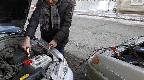 Мужчина прикуривает аккумулятор от другого автомобиля