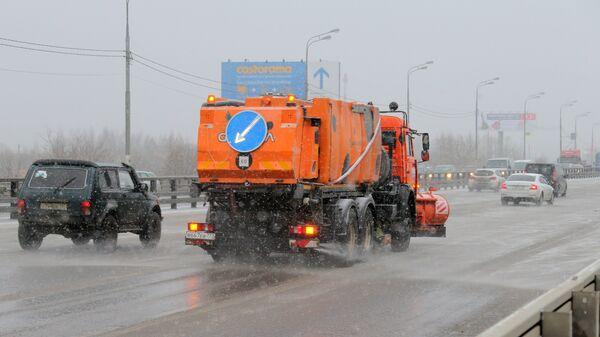 Снегоуборочная машина обрабатывает улицу противогололедным средством в Москве