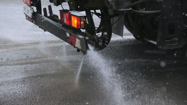 Снегоуборочная машина обрабатывает улицу противогололедным средством в Москве. Архивное фото