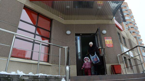Женщина с ребенком выходит из магазина Пятерочка