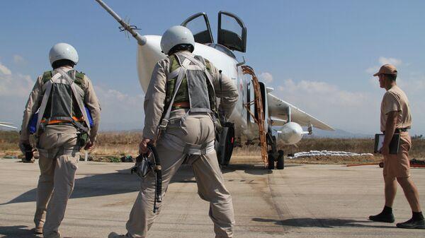 Российские летчики перед полетом у самолета Су-24 на авиабазе Хмеймим в Сирии