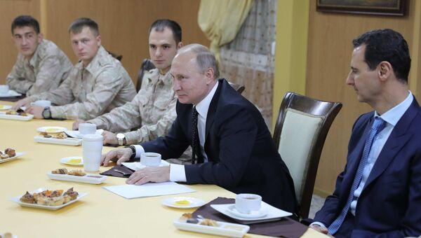 Президент РФ Владимир Путин и президент Сирийской Арабской Республики Башар Асад (справа) во время общения с военнослужащими авиабазы Хмеймим в Сирии