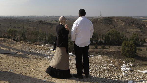 Израильтяне на фоне панорамы Сектора Газа на окраине израильского города Сдерот