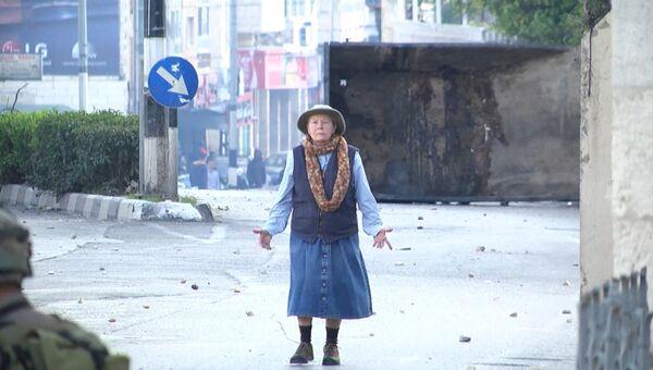 Безоружная пожилая женщина встала между солдатами и протестующими в Вифлееме