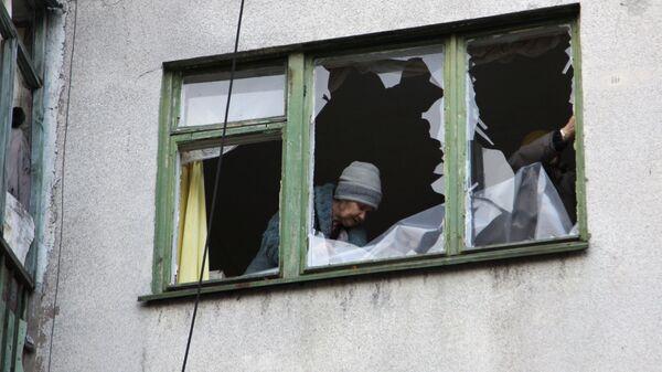 Женщина у окна жилого дома в центре города Ясиноватая, пострадавшего в результате обстрела