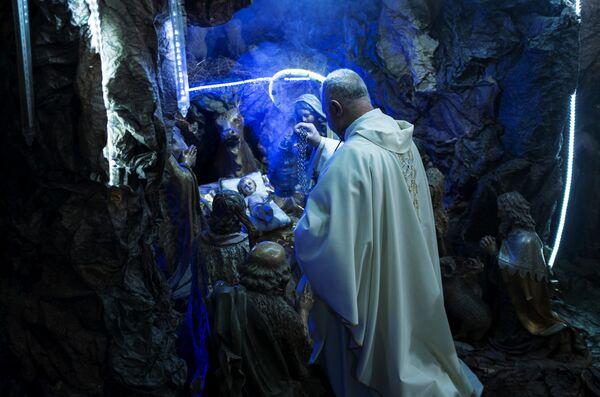 Священнослужитель, отец Мабдух помещает фигуру младенца Иисуса в рождественский вертеп во время празднования католического Рождества Христова в церкви Францисканцев Святой Земли в Каире