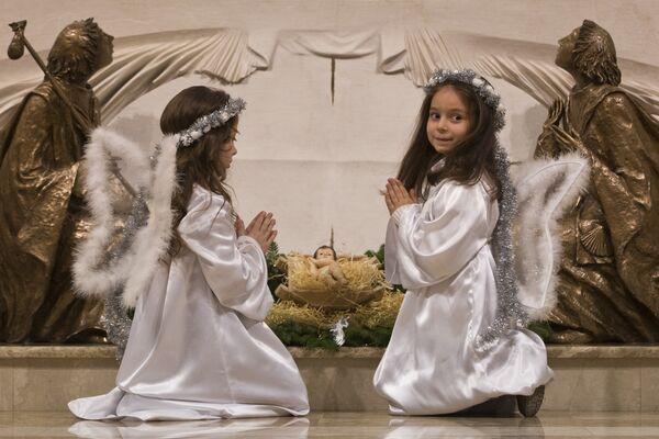 Дети молятся перед алтарем во время рождественской мессы в соборе Святой Матери Терезы в столице Косово Приштине