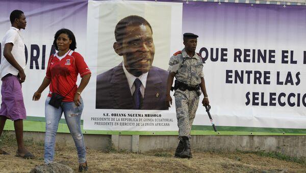 Сотрудник службы безопасности рядоом с портретом президента Экваториальной Гвинеи Теодоро Обианги Нгемы Мбасого. Архивное фото