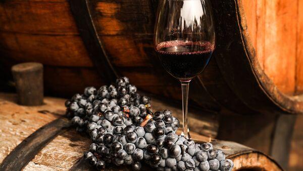 Виноградная лоза и вино в бокале на винодельческом предприятии Массандра в Крыму. Архивное фото.