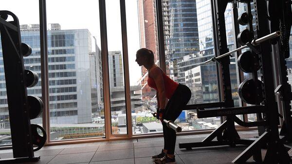 Девушка занимается со штангой в фитнес-клубе