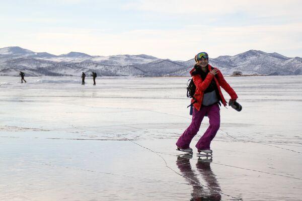 Девушка на коньках на льду озера Байкал