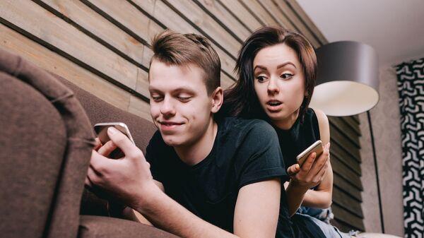 Молодая пара с мобильными устройствами. Архивное фото