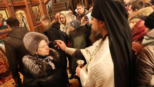 Верующие со священнослужителем во время традиционного праздничного молебна в Крещенский сочельник в Храме Святителя Николая в Измайловском Кремле в Москве