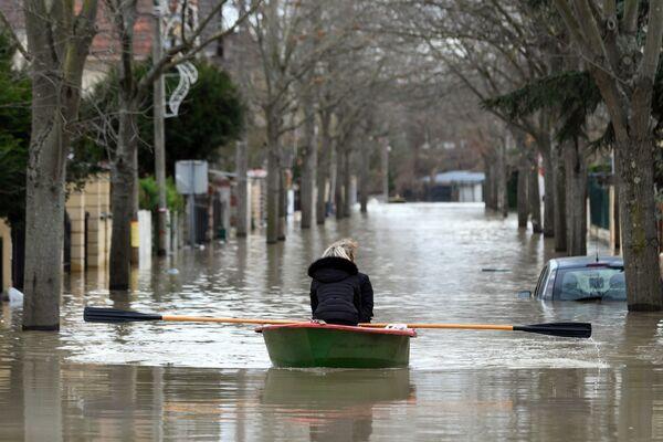 Местная жительница переправляется на лодке по одной из улиц в Париже, затопленной из-за прошедших ливневых дождей
