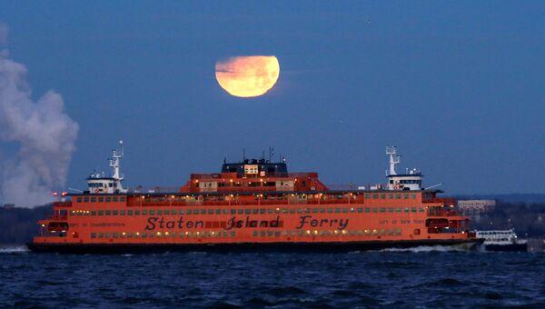 Полная луна садится позади парома на остров Статен-Айленд, США
