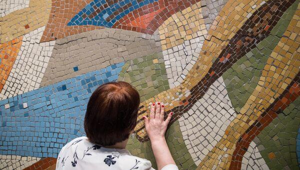 Антонина Захарченко трогает панно в музее современного искусства Гараж в Москве.