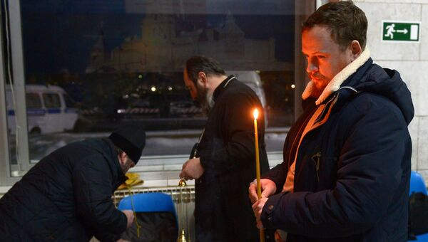 Мужчина ставит свечу в аэропорту Орска в память о пассажирах, погибших в результате крушения самолета Ан-148. 12 февраля 2018